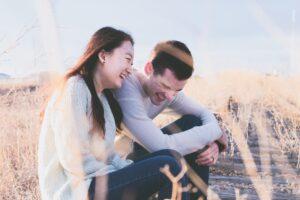 外に座り談笑している日本人女性と白人男性の画像