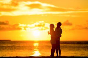 夕日をバックに仲睦まじい男女が抱き合い見つめあう画像