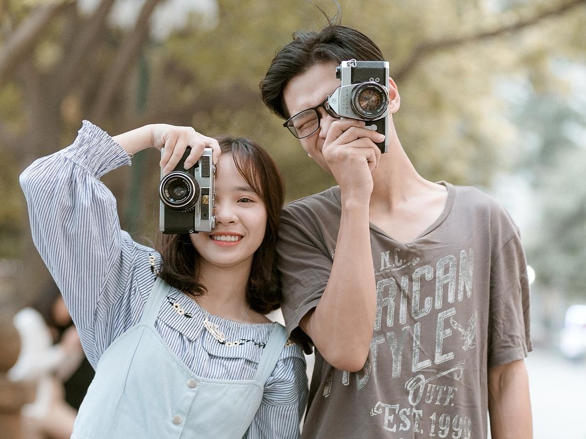 カメラで撮影する男女の画像