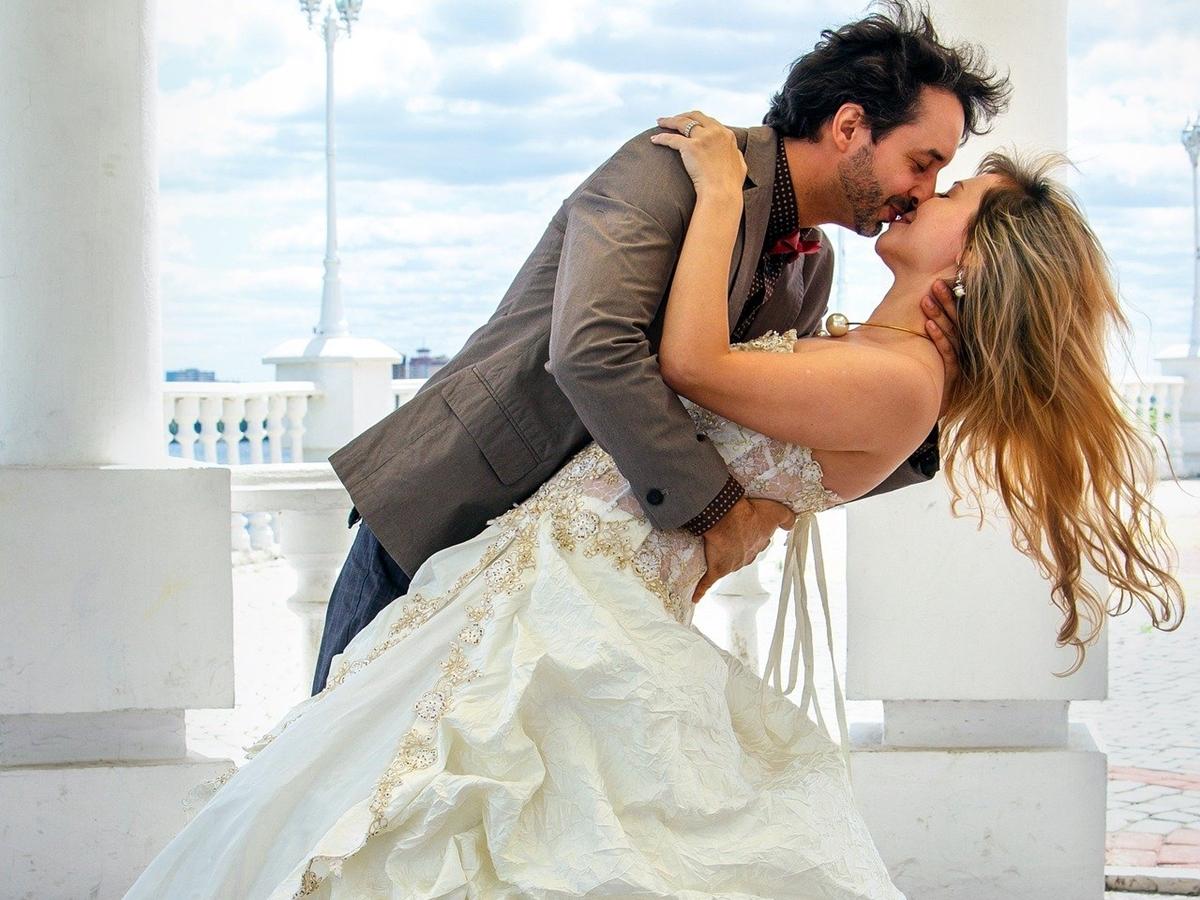 ウェディングドレスの女性にキスをする外国人カップルの画像